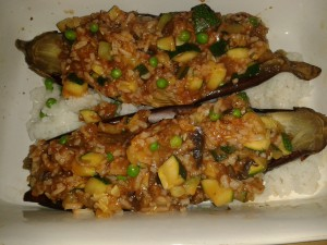 Use any leftover vegetables you have available to stuff aubergines.  These ones have rice, peas and mushrooms.