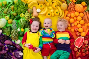 Small children surrounded by fruit and vegetables
