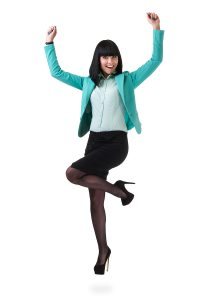 Successful young business woman happy for her success jumping. I