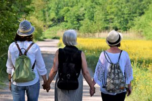 Women walking & holding hands